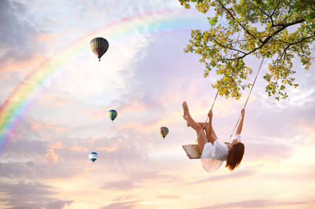 Dream world. Young woman swinging, hot air balloons in sunset sky on background