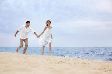 Happy couple running on beach, space for text. Romantic walk