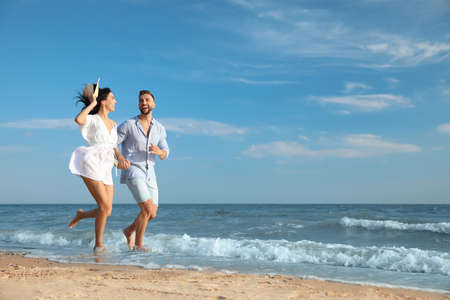 Happy young couple running together on beach Standard-Bild