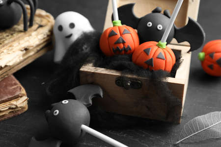 Different Halloween themed cake pops on black table, closeup