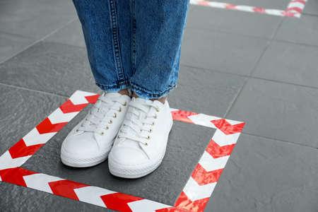 Woman standing on taped floor marking for social distance, closeup. Coronavirus pandemic