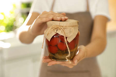 Woman holding jar of pickled tomatoes indoors, closeup