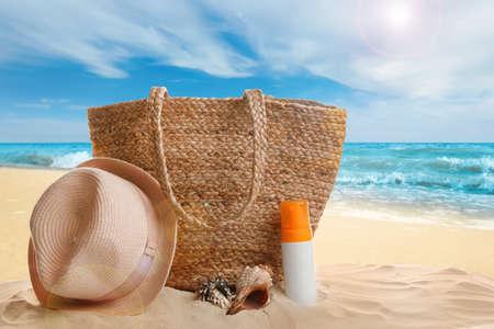 Different beach accessories on sand near ocean