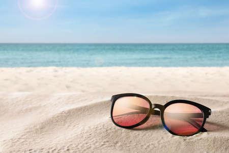 Stylish sunglasses on sandy beach near sea, space for text