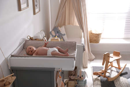 Cute little baby on changing table in room Banque d'images