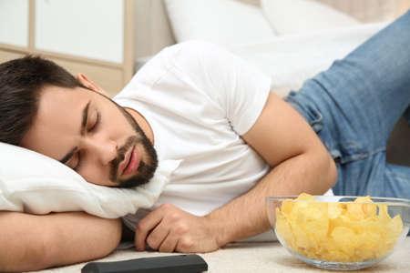 Lazy young man with bowl of chips and TV remote sleeping on floor at home