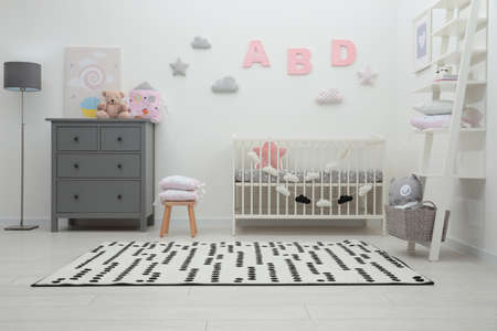 Cute baby room interior with crib and chest of drawers near white wall Stockfoto
