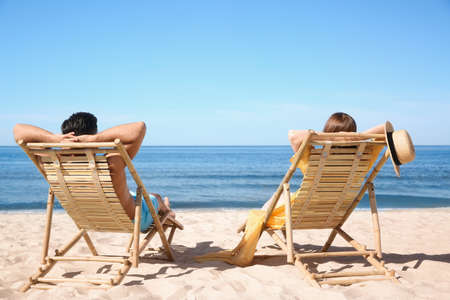 Woman and her boyfriend on deck chairs at beach. Lovely couple