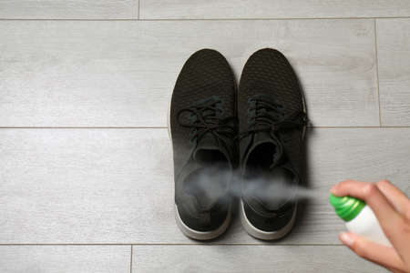 Woman spraying deodorant over pair of shoes at home, closeup. Space for text