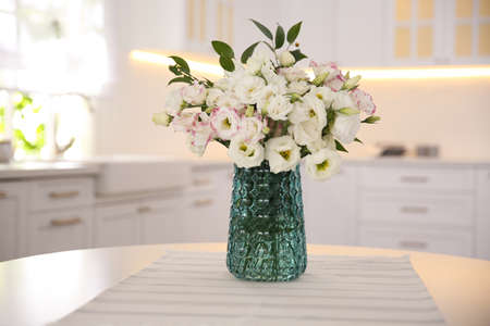 Bouquet of beautiful flowers on table in kitchen. Interior design Stockfoto