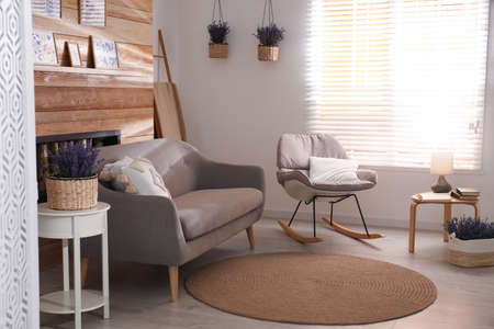 Stylish sofa and rocking chair in beautiful living room interior