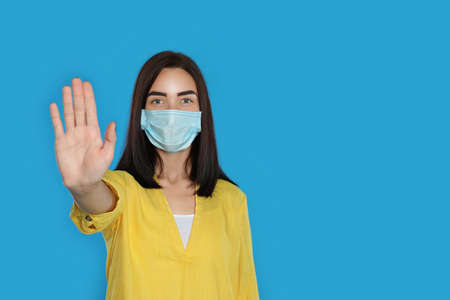 Young woman in protective mask showing stop gesture on light blue background, space for text. Prevent spreading of coronavirus Stock fotó - 155442303