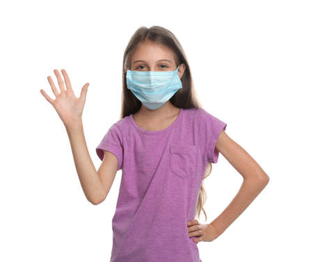 Little girl in protective mask showing hello gesture on white background. Keeping social distance during coronavirus pandemic