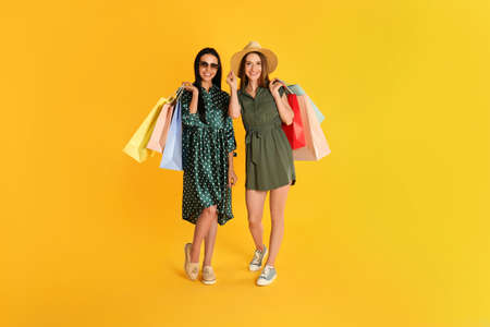 Beautiful young women with paper shopping bags on yellow background Stock fotó
