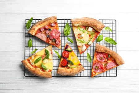 Slices of different delicious pizzas on white wooden table, flat lay Stock fotó - 155448132