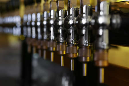 New modern beer taps in pub, closeup. Professional bar equipment