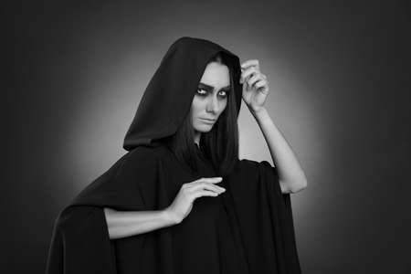 Mysterious witch with spooky eyes on dark background. Black and white effect