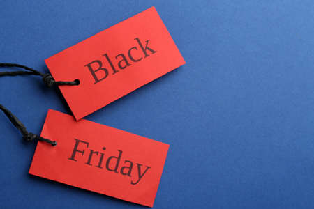 Red tags with words BLACK FRIDAY on blue background, flat lay. Space for text