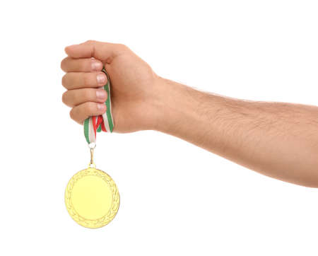 Man holding golden medal on white background, closeup. Space for design