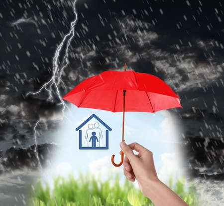Insurance agent covering illustration with red umbrella during thunderstorm, closeup