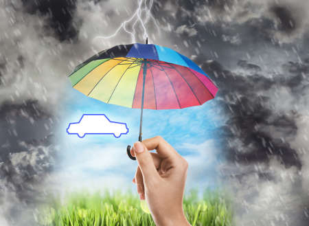 Insurance concept. Woman protecting car illustration with rainbow umbrella from storm, closeup Stock fotó