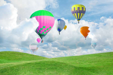 Fantastic dreams. Hot air balloons in sky with fluffy clouds over green meadow Foto de archivo