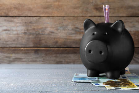 Black piggy bank with money on wooden table, space for text