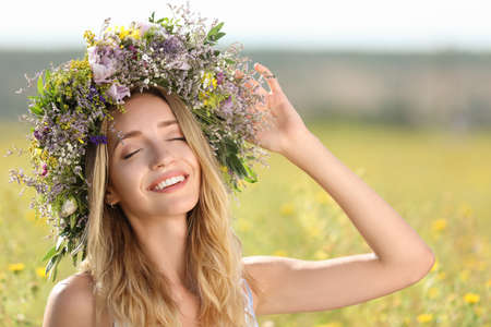 Young woman wearing wreath made of beautiful flowers in field on sunny day Stock fotó - 155445423