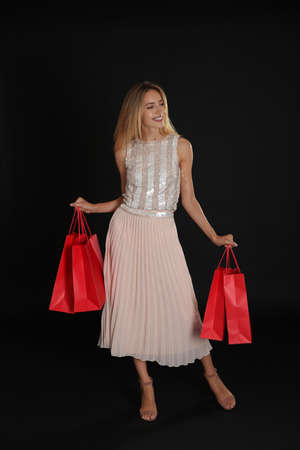 Happy young woman with shopping bags on dark background. Black Friday Sale Stock fotó