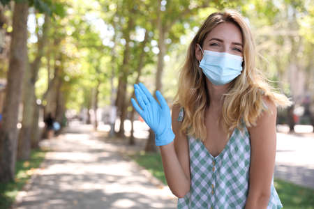 Woman in protective face mask showing hello gesture outdoors. Keeping social distance during coronavirus pandemic