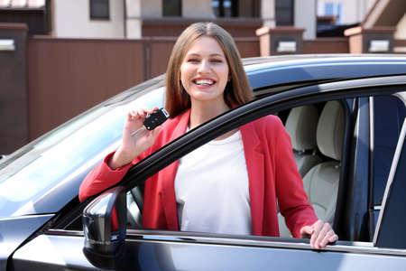 Happy woman with car key near her new auto outdoors Archivio Fotografico