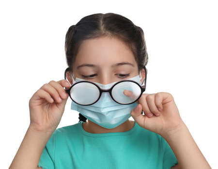 Little girl wiping foggy glasses caused by wearing medical face mask on white background. Protective measure during coronavirus pandemic