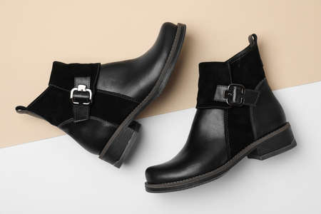 Stylish black female boots on color background, flat lay