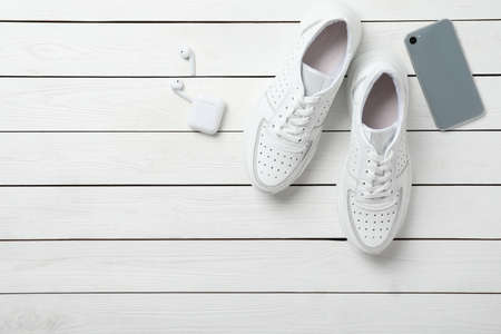 Pair of stylish shoes, modern smartphone and wireless earphones on white wooden table, flat lay. Space for text Stock fotó