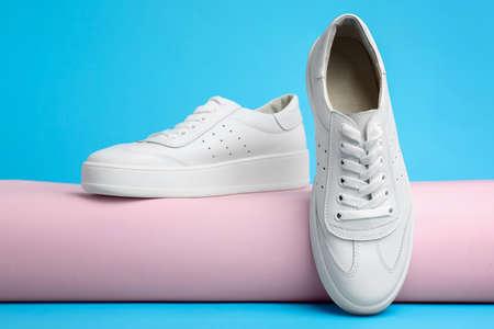 Stylish white shoes on light blue background