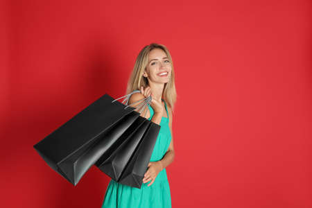 Happy young woman with shopping bags on red background, space for text. Black Friday Sale
