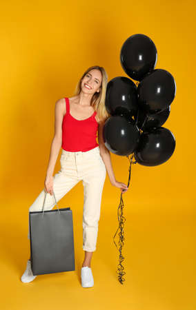 Happy young woman with balloons and shopping bag on yellow background. Black Friday Sale