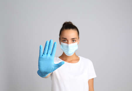 Woman in protective mask showing stop gesture on gray background. Prevent spreading of COVID-19