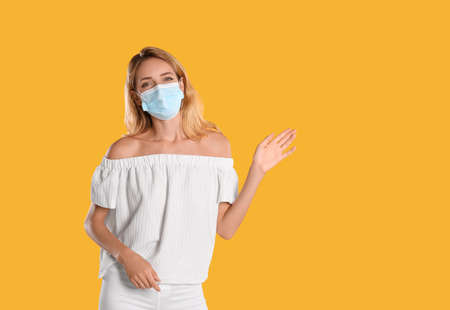 Woman in protective face mask showing hello gesture on yellow background, space for text. Keeping social distance during coronavirus pandemic Stock fotó