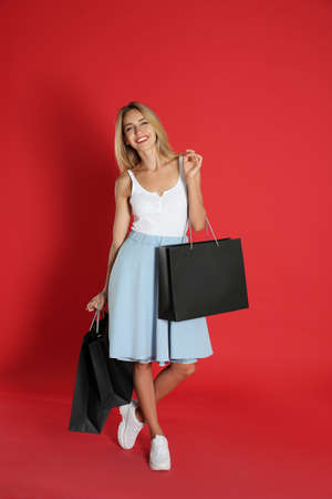 Happy young woman with shopping bags on red background. Black Friday Sale Stock fotó