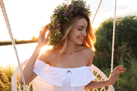 Young woman wearing wreath made of beautiful flowers on swing chair outdoors at sunset