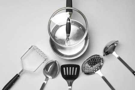 Set of modern cooking utensils on light gray background, flat lay