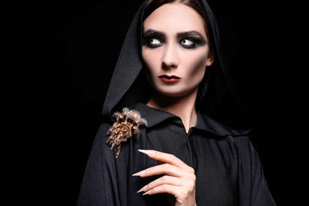Mysterious witch with spooky spider on black background