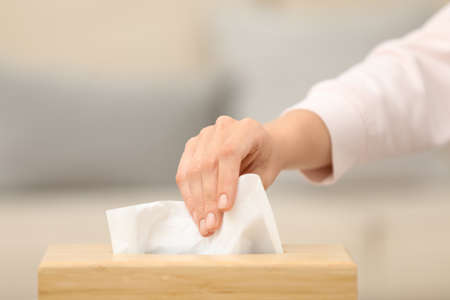 Woman taking paper tissue from holder indoors, closeup