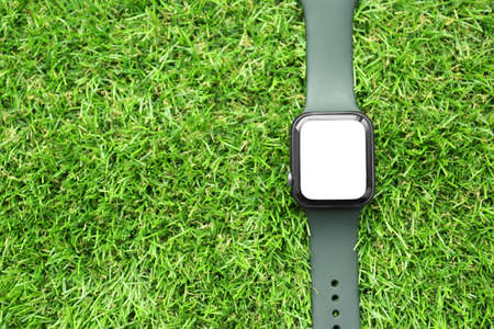Stylish smart watch on green grass, top view. Space for text