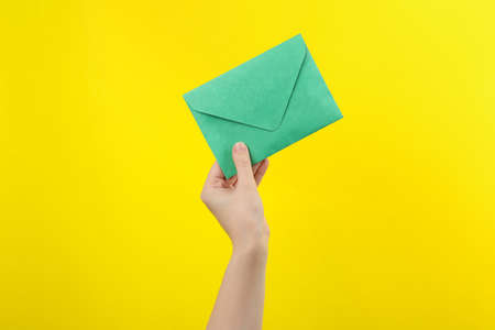 Woman holding green paper envelope on yellow background, closeup Stock Photo