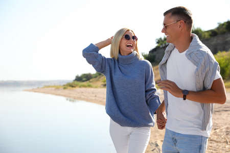 Happy couple in stylish sweaters on beach