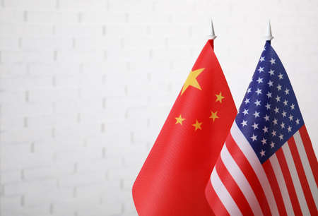 USA and China flags against white brick wall, space for text. International relations