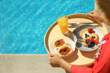 Young woman with delicious breakfast on tray near swimming pool, closeup. Space for text