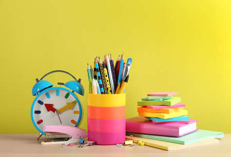 Set of school stationery and alarm clock on table against yellow background. Back to school